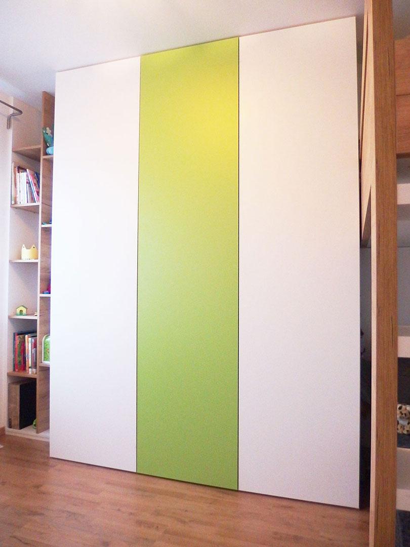 Vestavěná skříň s pantovými dveřmi v kombinaci bílé a zelené s otevřenými dřevěnými regály.