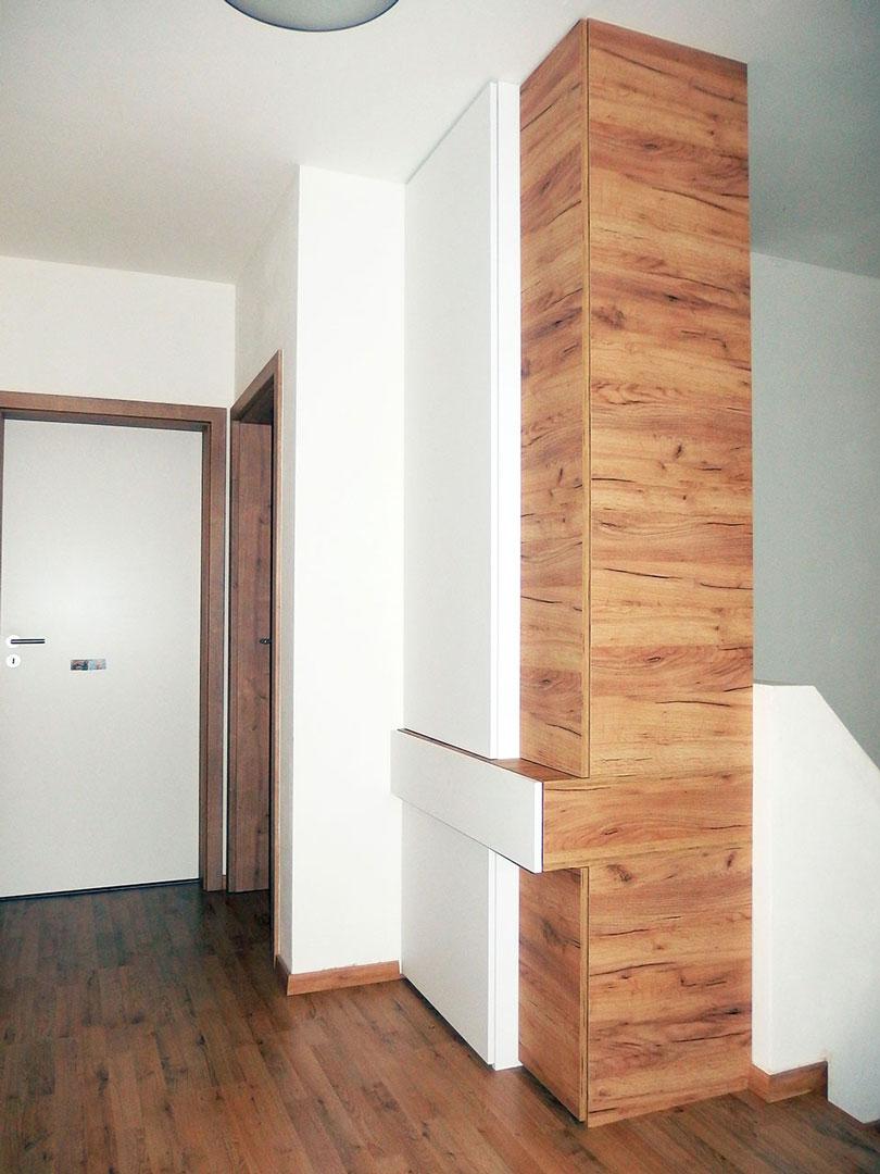 členitý vestavěná skříň se šuplíkem a pantovými dveřmi v kombinaci bílé barvy a dřevěného dekoru.