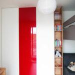 Vestavěná skříň s pantovými dveřmi v bílé barvě kombinovaná s červenými skleněnými dveřmi a dřevěnou otevřenou částí.
