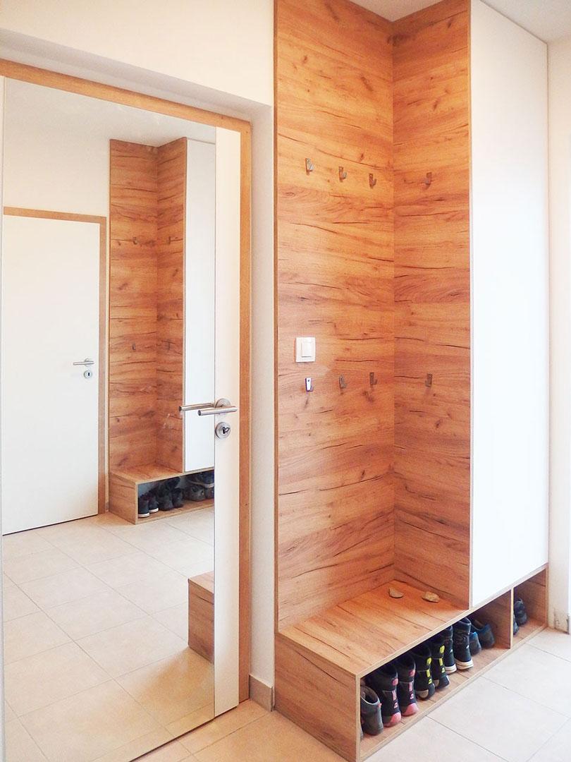 Skříň do chodby s věšáky v dubovém provedení s bílými pantovými dveřmi.