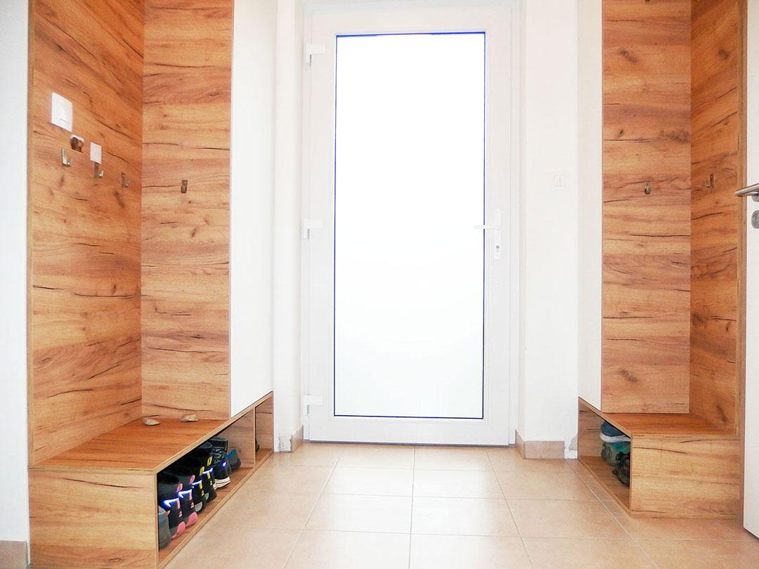 Vestavěné skříně do chodby s otevřeným botníkem v dubovém dekoru s bílými dveřmi.