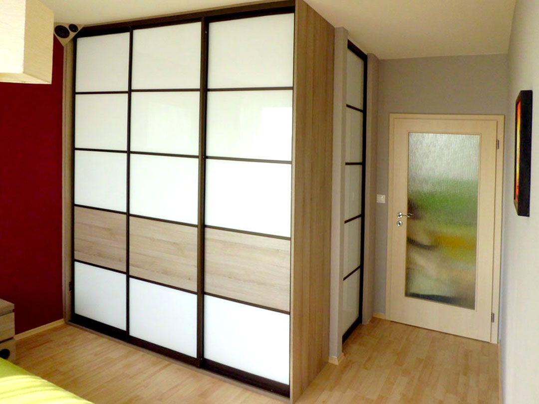 Vestavěná skříň do ložnice s posuvnými dveřmi s výplní bílé lakované sklo.