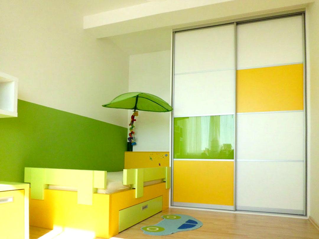Dětský pokoj s postelí a vetsavěnou skříní s posuvnými dveřmi.