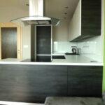"""Kuchyň na míru do """"U"""" v bílé barvě a tmavém dřevěném dekoru."""