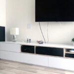Obývací stěna s bílými šuplíky a otevřenými částmi v kombinaci bílé barvy a světlého dřeva.