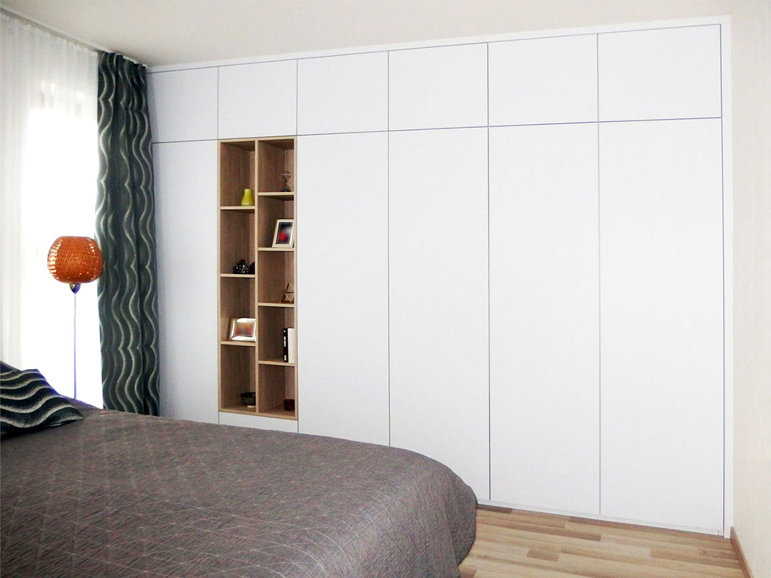 Vestavěná skříň do ložnice s pantovými dveřmi v bílé matné barvě.