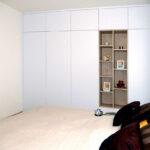 Vestavěná skříň do ložnice v bílé maté barvě s otevřenou dřevěnou částí.