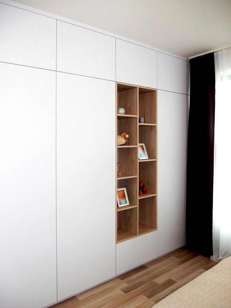 Bílá pantová skříň na míru s otevřenými dřevěnými policemi.