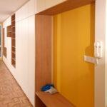 Realizace pantové skříně na míru v bílé barvě kombinované s dřevěnými prvky.