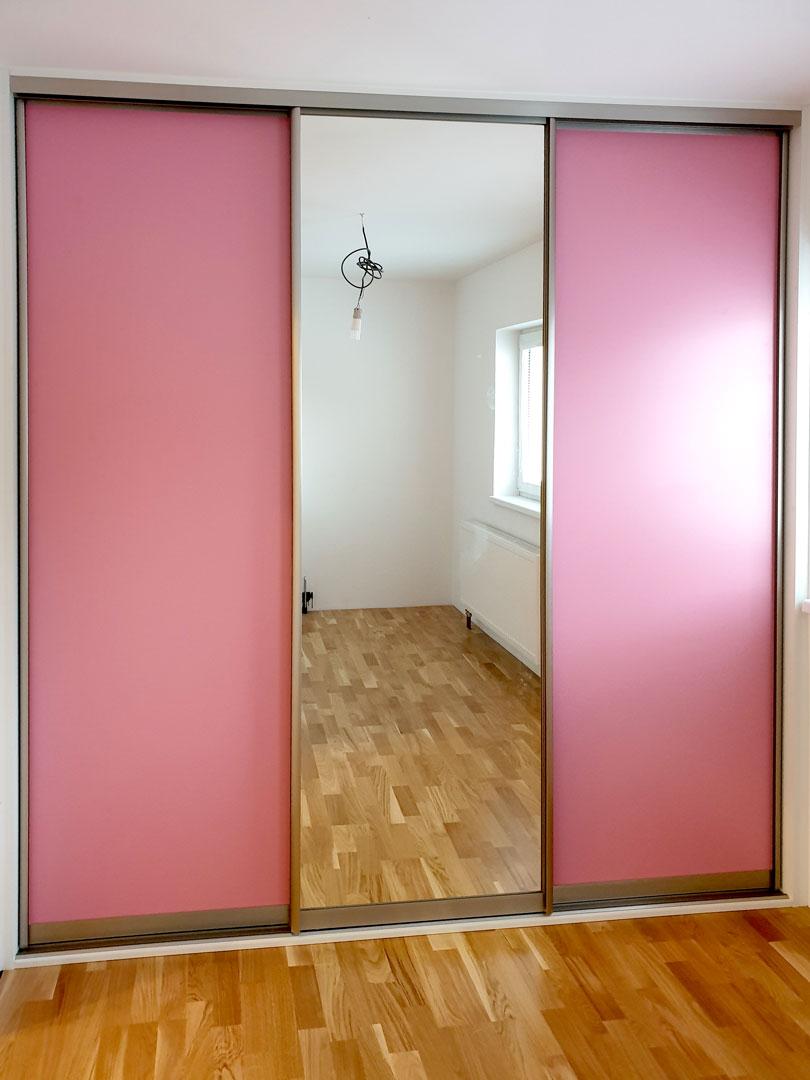 Skříň na míru s posuvnými dveřmi v růžové barvě se zrcadlem.