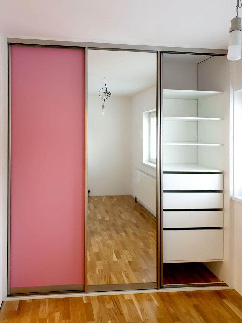 Vestavěná skříň s částečně otevřenými posuvnými dveřmi.