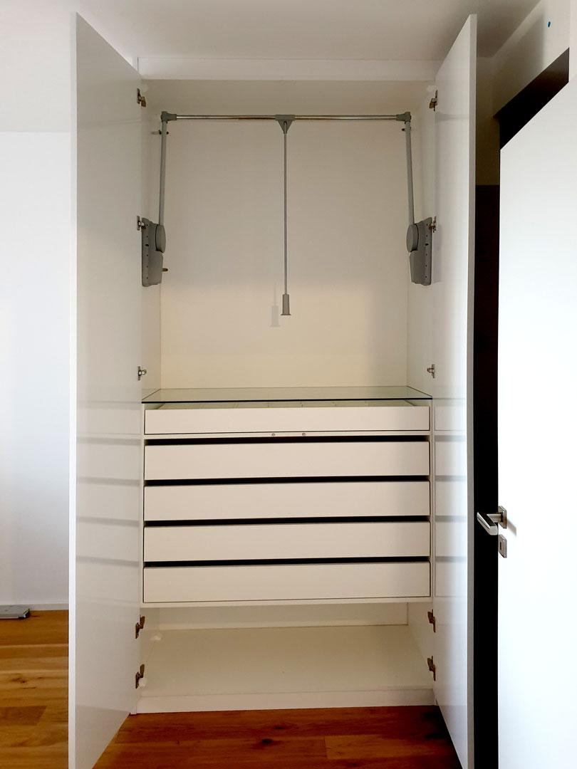 Otevřený pantový skříň se šuplíky a sklopnou šatní tyčí.