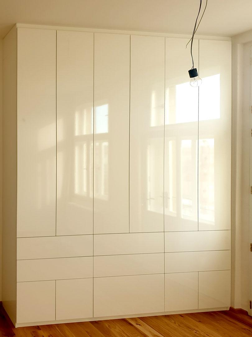 Realizace vestavěnéí skříně s pantovými dveřmi a šuplíky v bílém lesku.
