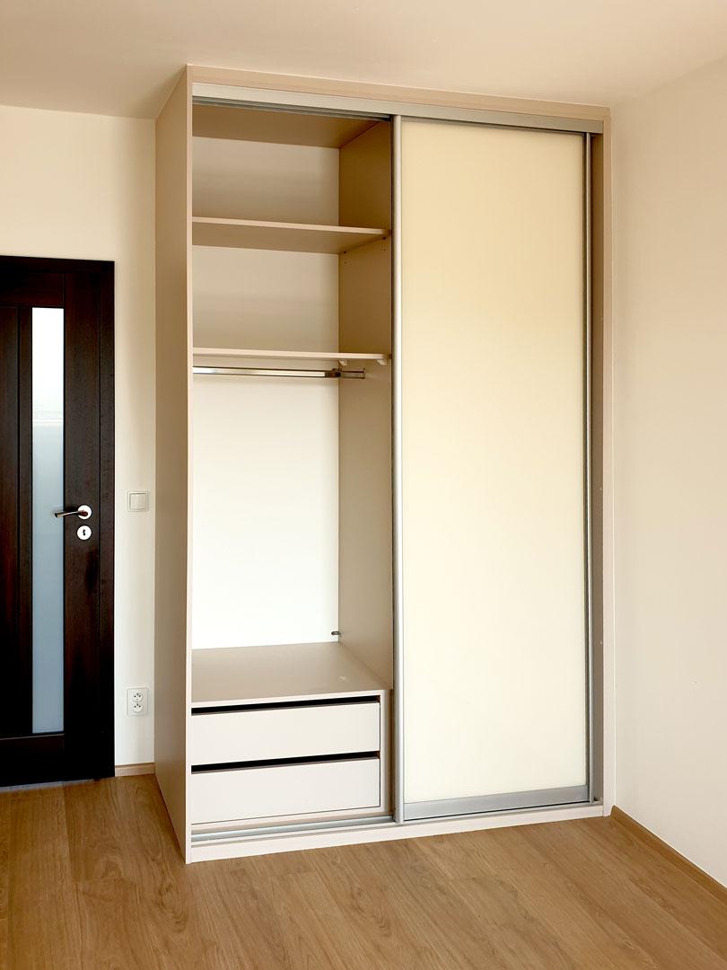 Interier vestavěné skříně na míru s posuvnými dveřmi.