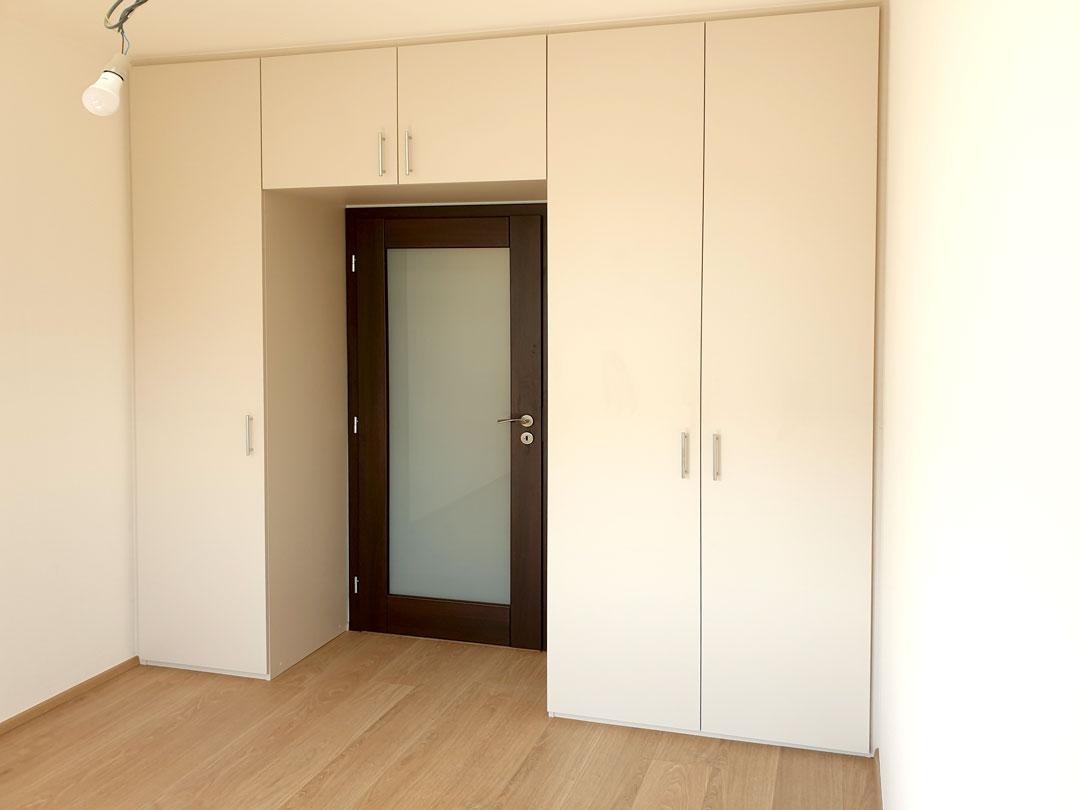 Realizace skříně do ložnice s pantovými dveřmi v bílé barvě.