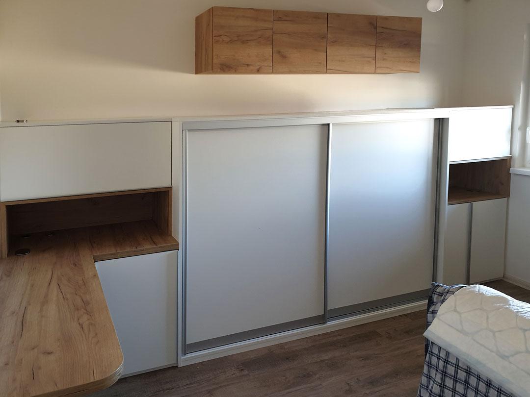 Nízká skřín na míru do ložniec s posuvnými i pantovými dveřmi a pracovním stolem.