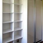Realizace vestavěné skříně s posuvnými dveřmi a otevřenámi policemi v bílé barvě.