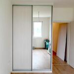 Realizace skříně na míru s posuvnými dveřmi. Kombinace světlého dřeba a zrcadla.