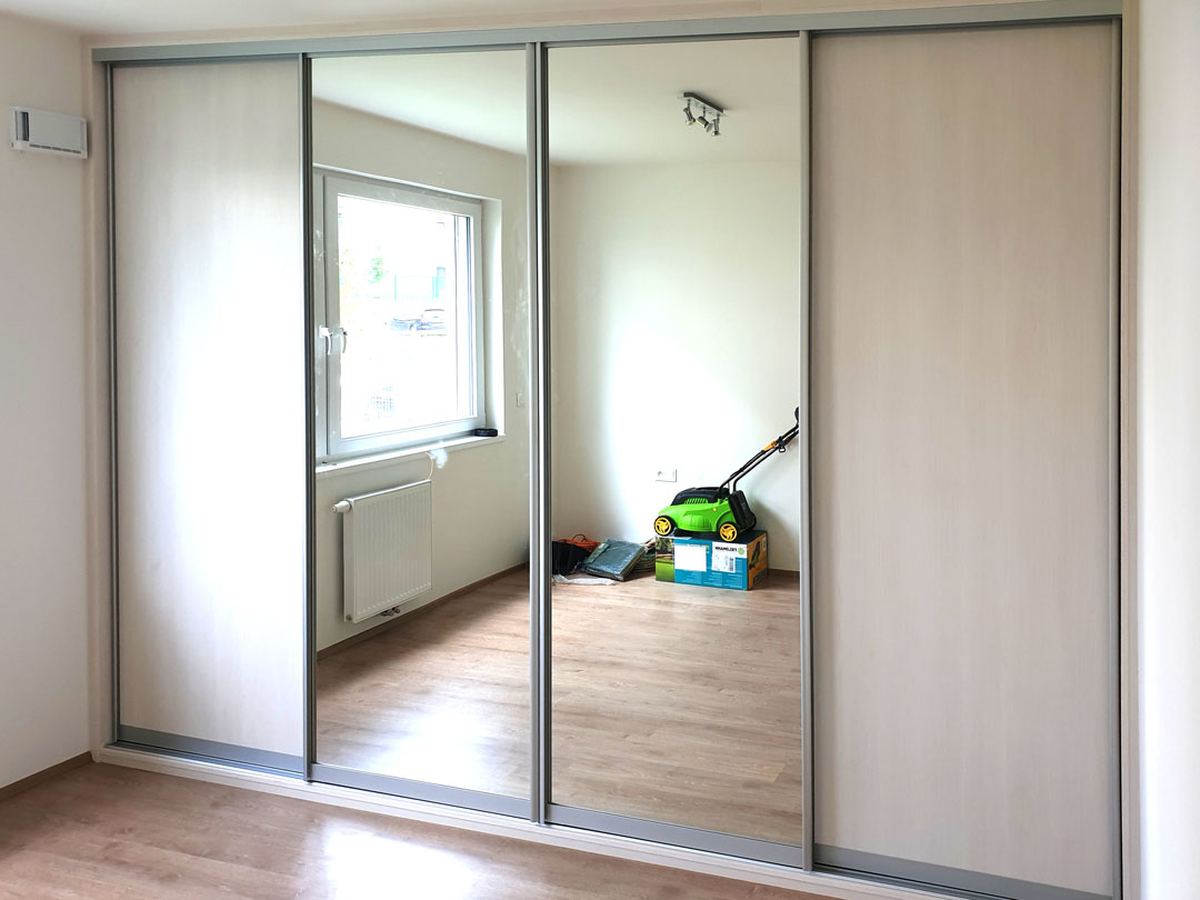 Realizace skříně na míru do ložnice s posuvnými dveřmi. Kombinace světlého dřeva a zrcadel.