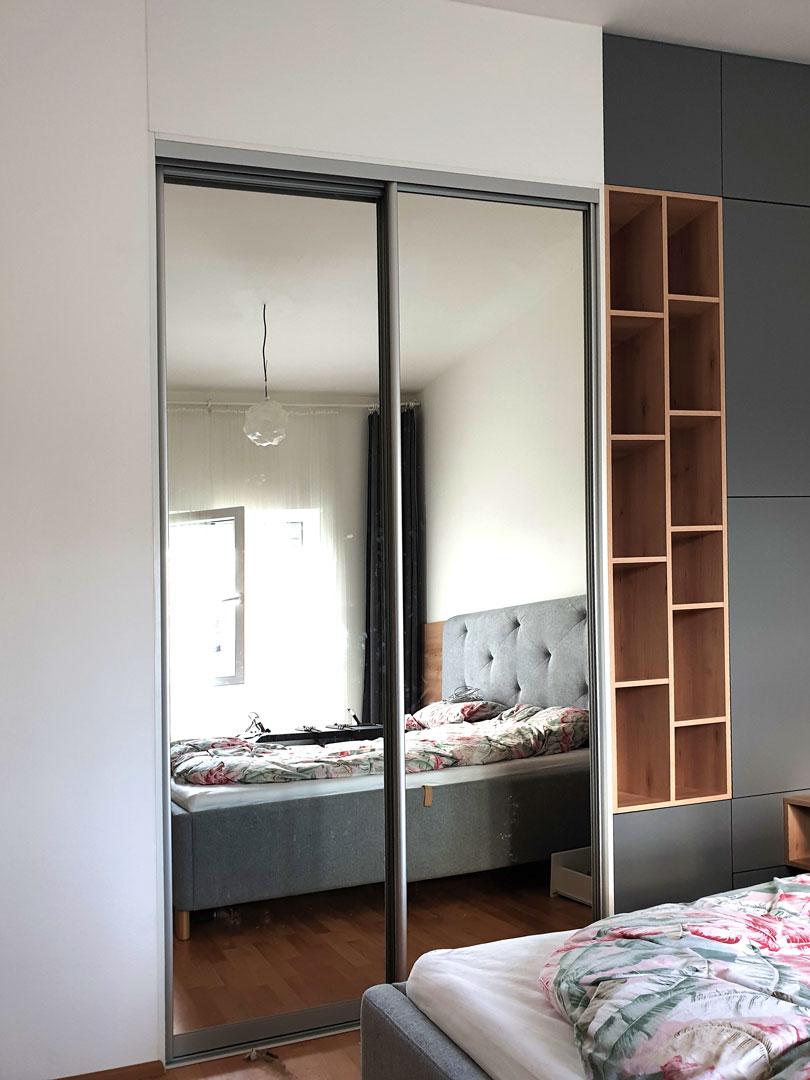 Realizace šatny na míru do ložnice s kombinací posuvných dveř, pantových dveří a dřevěné otevřené části.