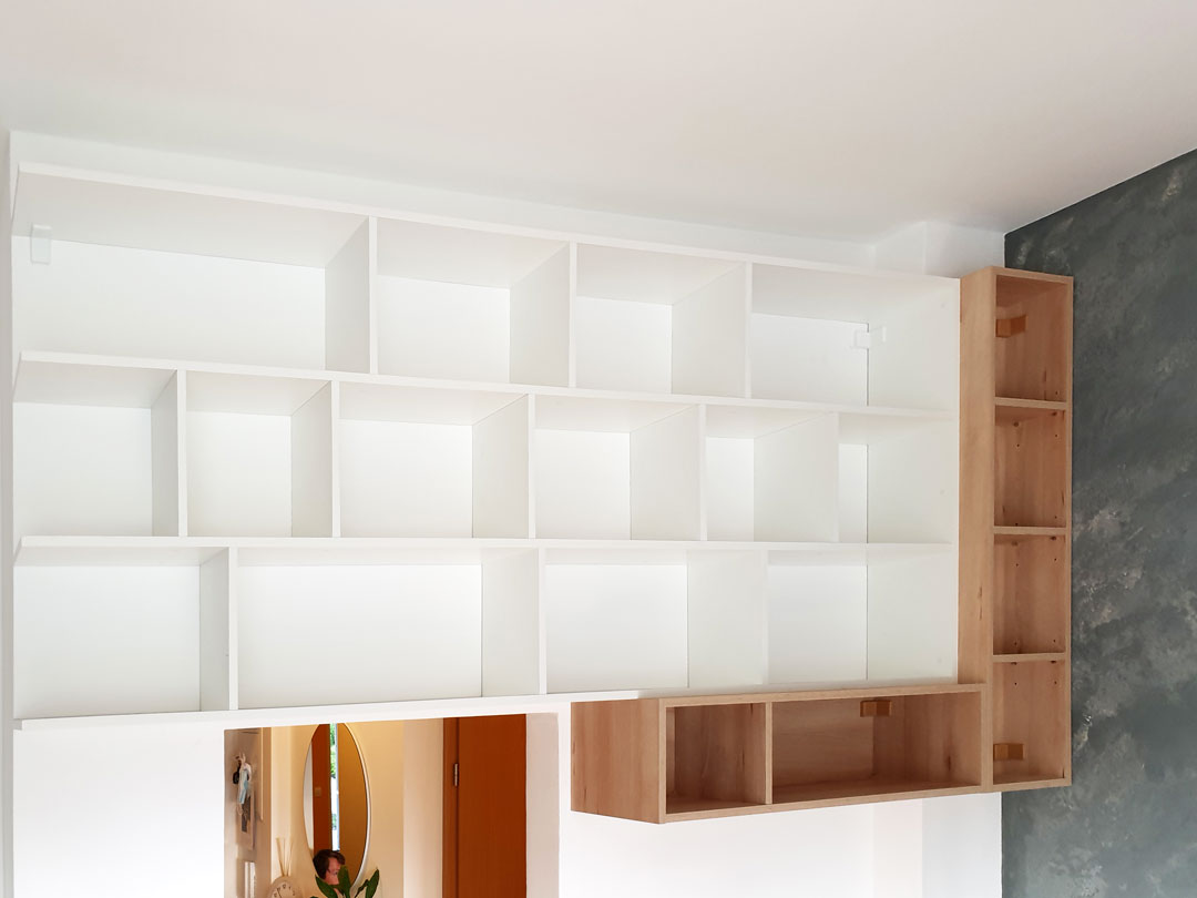 Otevřené police so ložnice v kombinaci bílé a přírodního dubu.