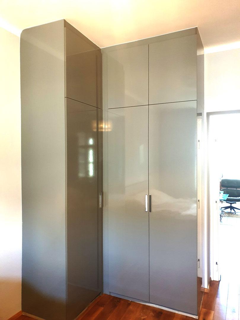 Rohová vestavěná skříň do chodby v lesklé šedé barvě.