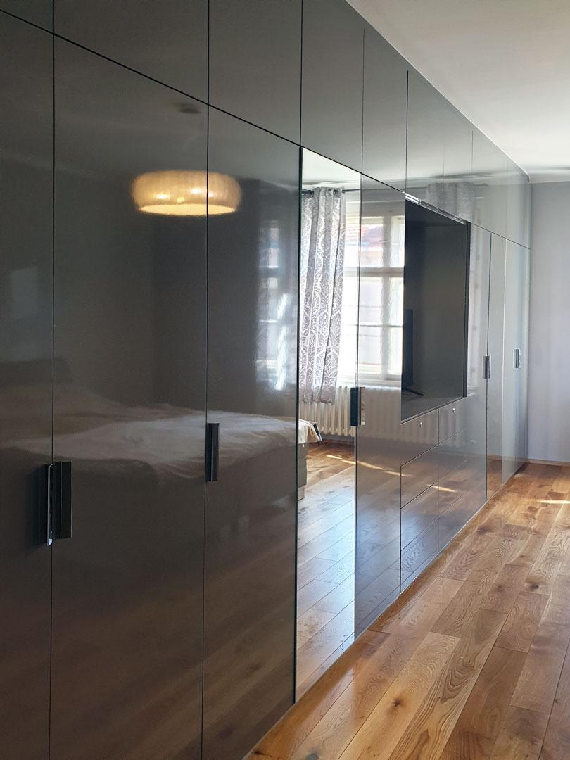 Velké pantová skříň do ložnice s prostorem na televizi v šedé lesklé barvě.