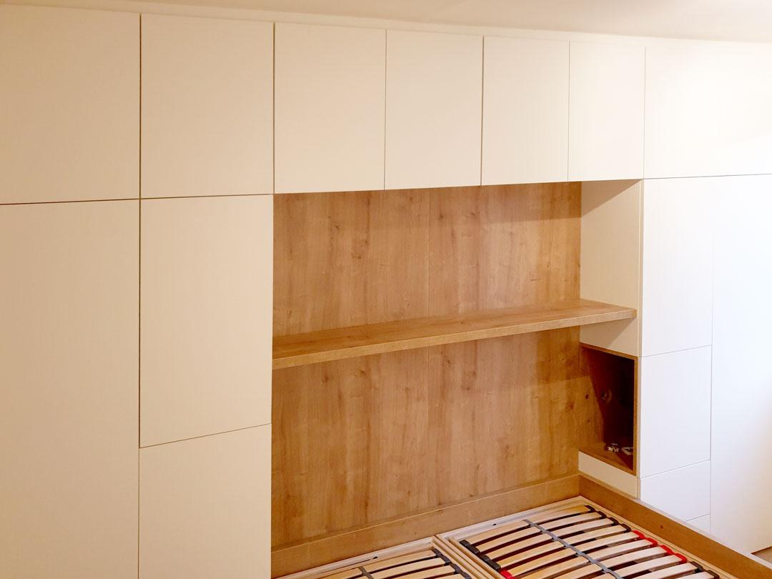 Obestavěná postel skříní s pantovými dveřmi.