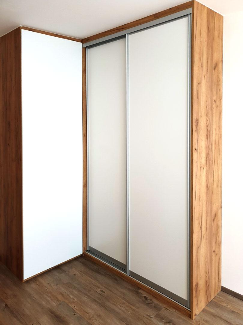 Vestavěná rohová skříň v přírodním dubovém dekoru s bílými dveřmi.