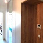 Realizace vestavěné skříňě do chodby s otevřenou dřevěnou částí a pantovými dveřmi.