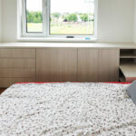 Snížená skříň na míru do ložnice pod okno s pantovými dveřmi a šuplíky.