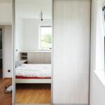 Realitace skříně na míru do ložnice s posuvnými dveřmi ve světlém dřevěném dekoru a zrcadlovými dveřmi.