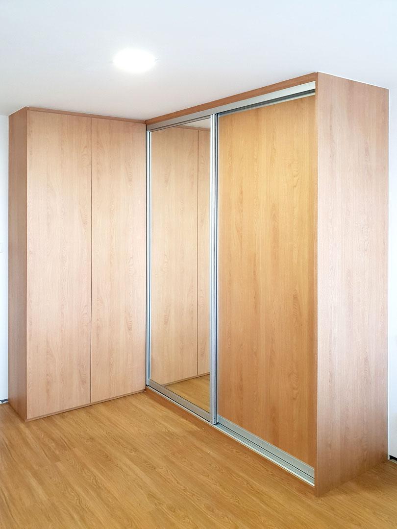 Rohová vestavěná skříň s pantovými a posuvnými dveřmi v dubovém dekoru.