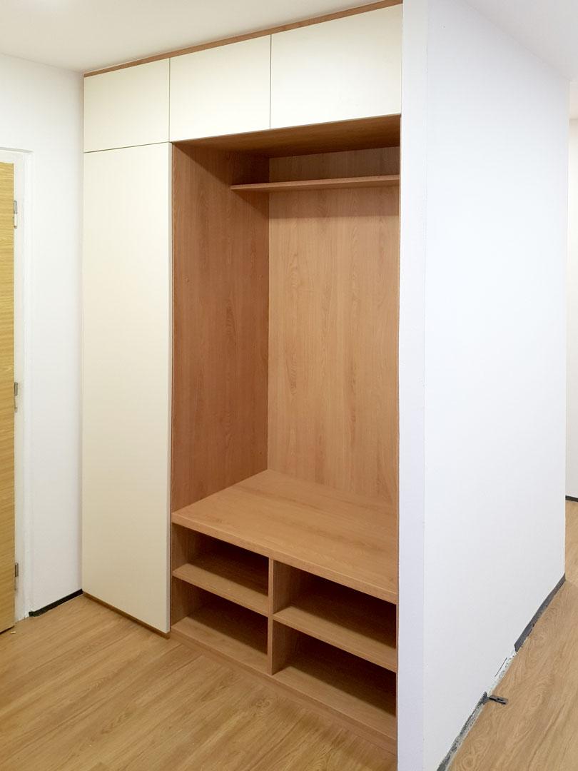 Realizace vestavěné skříně do chodby s botníkem, prostorem na věšáky a pantovými dveřmi.