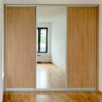 Vestavěná skříň do ložnice s posuvnými dveřmi s jedním zrcadlem.
