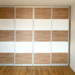 Realizace vestavěné skříně s posuvnými dveřmi do ložnice. Dveře jsou horizontálně dělené na pět částí.