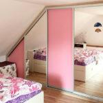 Realizace vestavěné skříně do ložnice v podkroví se zrcadlovými a růžovými dveřmi.