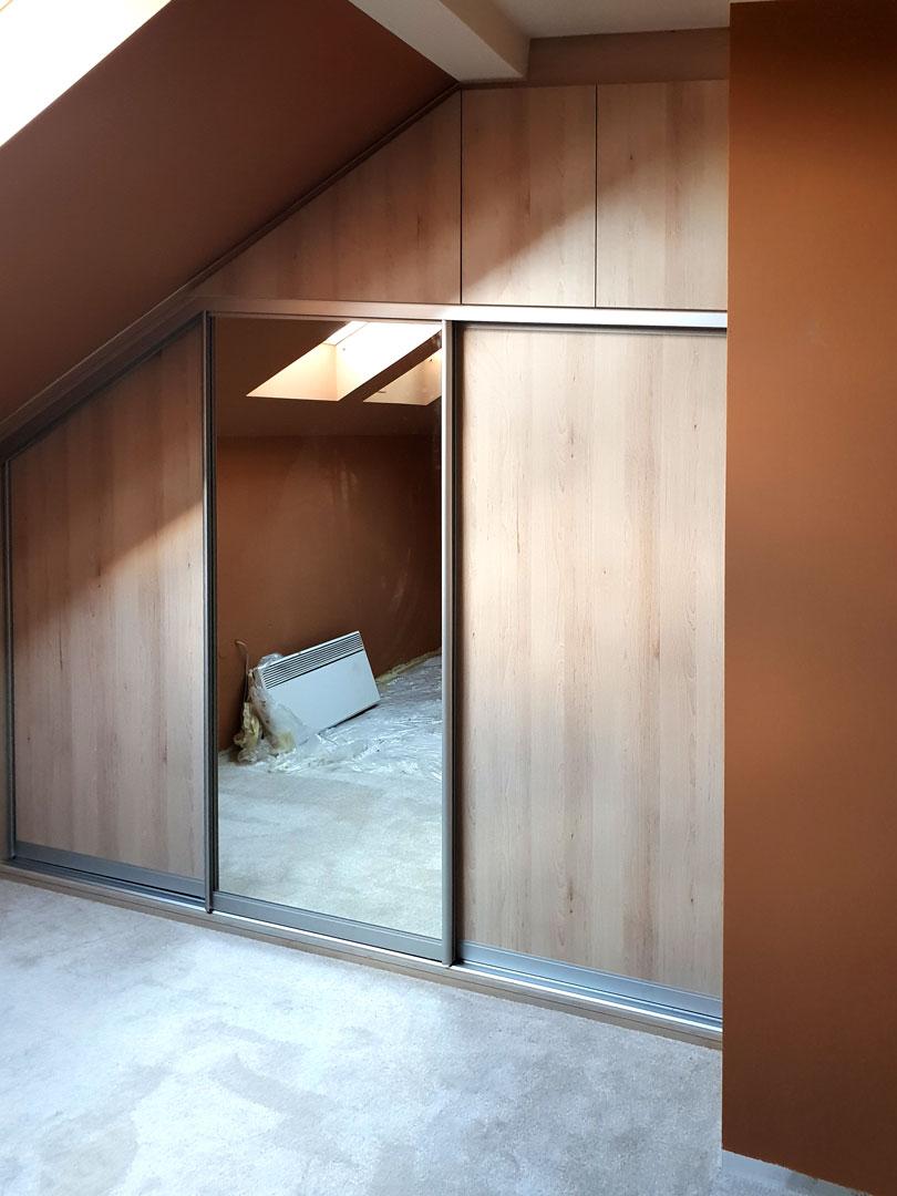 Vestavěné skříň do podkroví s posuvnými a pantovými dveřmi v dekoru dřeva.