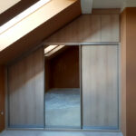 Skříň na míru do ložnice v podkroví v dekoru dřeva s kombinovanými posuvnými a pantovými dveřmi.