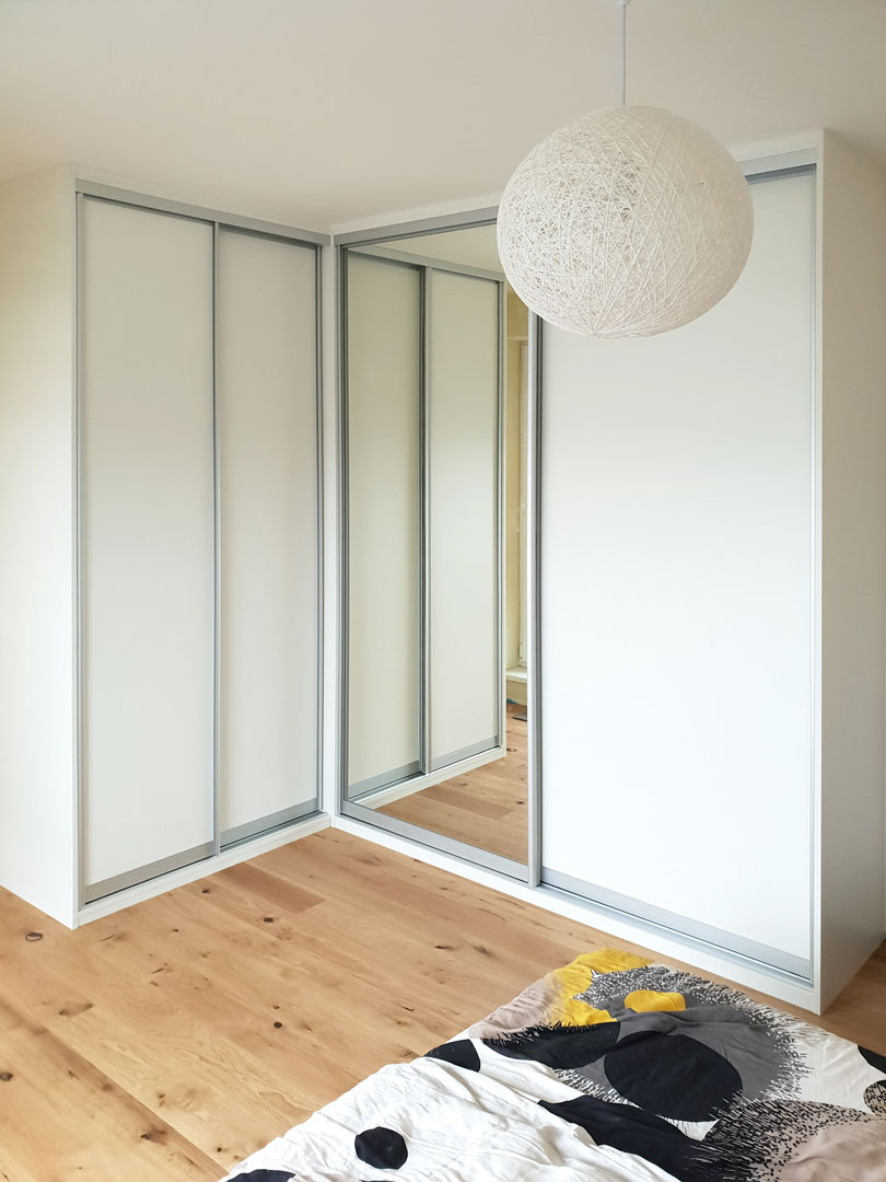 Rohová skříň na míru do ložnice s posuvnými dveřmi v hliníkovím rámu v bílé barvě.