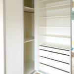 Interier rohové skříně na míru s posuvnými dveřmi v bílé barvě.