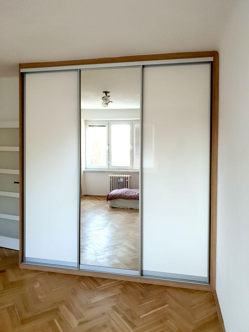 Realizace vestavěné skříně s posuvnými dveřmi v kombinaci zrcadla a lakovaného skla / lacobelu
