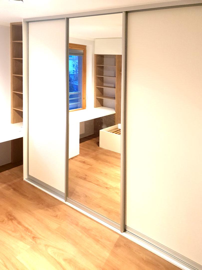 Realizace skříně na míru s posuvnými dveřmi a zakomponovaným pracovním stolem.