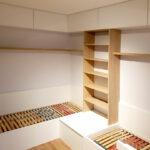 Realizace dětského pokoje se dvěmi postelemi a skříněmi.