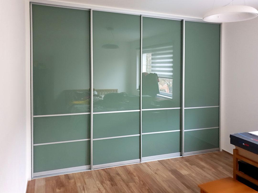 Realizace vestavěné skříně na míru s posuvnými dveřmi v hliníkovím rámu. Jako výplň byl použit zelený lacobel.