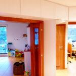 Vestavěné skříně an míru do chodby obestavující prostor kolem interierových dveří.