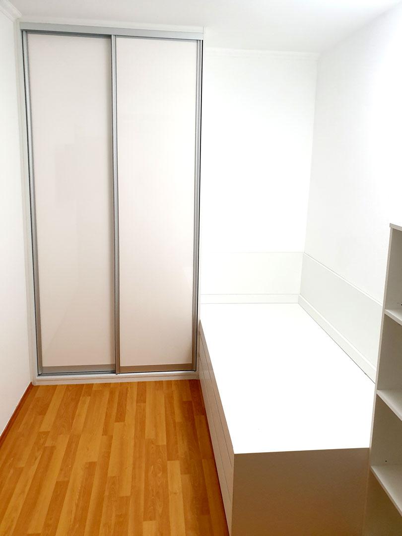 Realizace vestavěné skříně s posuvnými dveřmi s postelí a otevřenou regálem. Vše v bílé barvě.