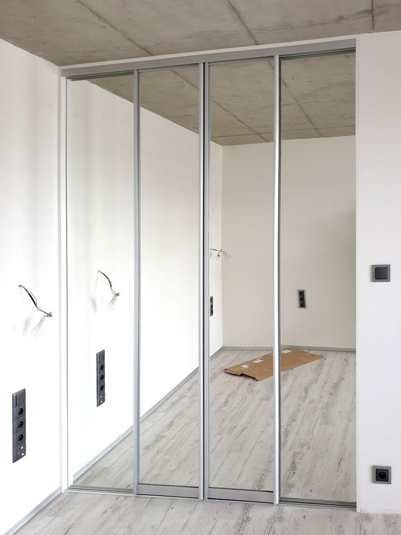 Realizace šatny uzavřené posuvnými zrcadlovými dveřmi ve stříbrném hliníkovém rámu.