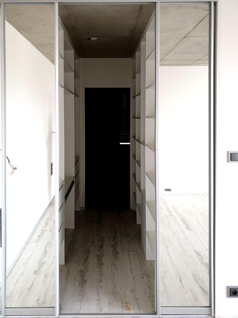 Realizace šatny na míru uzavřené zrcadlovými posuvnými dveřmi. Pohled do otevřené šatny.