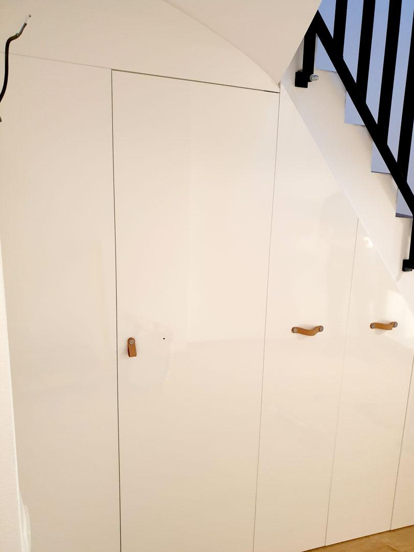 Realizace vestavěné skříně s pantovými dveřmi do prostoru pod schody v bílé barvě.
